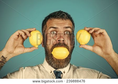 Dieting And Fitness. Surprised Man With Long Beard Eat Lemon. Vitamin Citrus At Hipster On Blue Back