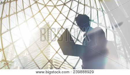 Silhouette Of Young Intelligent Man Managing A Computer In Modern Office Environment With Copy Space