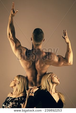 Man Bodybuilder With Muscular Back Raise Hands Biceps, Triceps, And Girls Or Women With Long Blond H