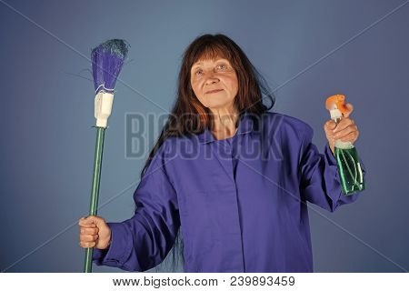 Cleanup and order services. Housekeeper woman in uniform with clean spray. Woman with long hair hold soup bottle. Cleaning and purity. Old lady cleaner with broom on blue background. poster