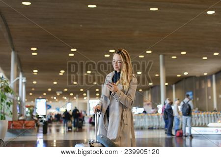 Girl Standing In Airport Waiting Room With Valise And Using Smartphone. Concept Of Traveling Abroad