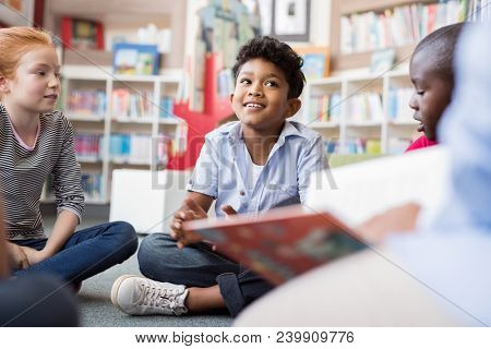 Multiethnic group of kids sitting on floor in circle around the teacher and listening a story. Discussion group of children inaa library talking to woman. Smiling hispanic boy in elementary school.
