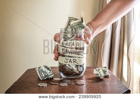 Hand grabbing a swear jar filled with money