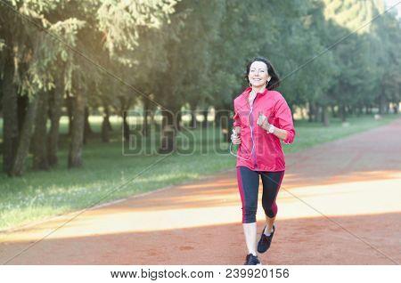 Portrait Of Elderly Woman Running In The Park