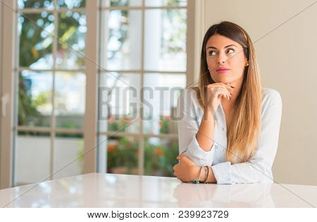 Young beautiful woman at home thinking and looking up expressing doubt and wonder