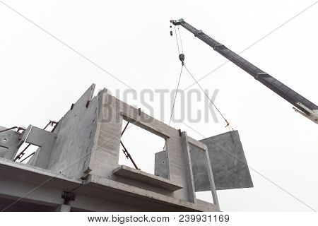 Construction Site Crane Is Lifting A Precast Concrete Wall Panel To Installation Building. Isolated