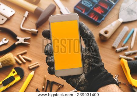Handyman Smart Phone App With Blank Screen. Repairman Holding Telephone In Hand. Copy Space For Text