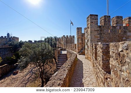 Lisbon, Portugal - February 1, 2013: Castelo de Sao Jorge aka Saint George Castle. Defensive walls with a view of the wallwalk, battlements, ramparts, merlons and crenels in the towers