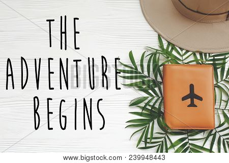 The Adventure Begins Text On Passport With Plane And Hat With Green Palm Leaves On White Wooden Back