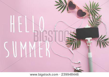 Hello Summer Text On Stylish Pink Sunglasses, Phone On Selfie Stick, Headphones, And Green Palm Leav