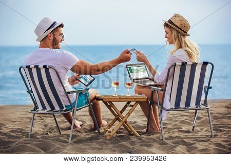 Happy Smiling Couple Surfing The Net And Enjoy The Summer At Tropical Beach Using Laptop, Digital Ta