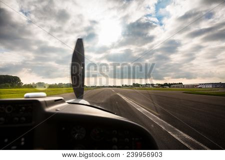 Sport pilot landing on airfield strip with propeller aircraft