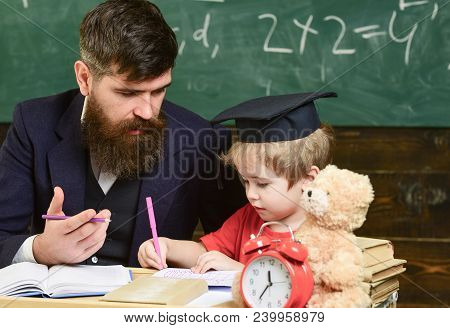 Elementary Education. Teacher In Formal Wear And Pupil In Mortarboard In Classroom, Chalkboard On Ba
