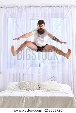 Man In Shirt And Underpants Jumping On Bed, White Curtains On Background. Macho With Beard Jumps Hig