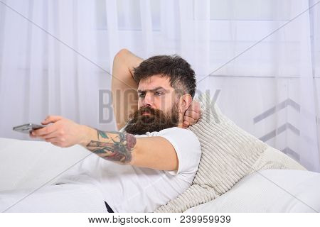 Man Laying On Bed, Watching Tv, White Curtains On Background. Macho With Beard Holds Smartphone As C