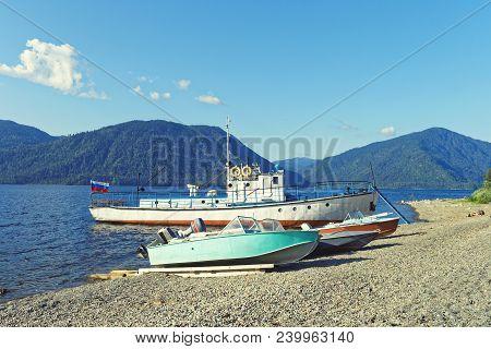 Siberia, Teletskoye Lake. Passenger Vessel And Motor Boats Moored Near The Shore