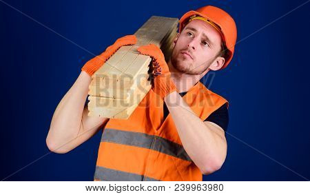 Carpenter, Woodworker, Strong Builder On Thoughtful Face Carries Wooden Beam On Shoulder. Wooden Mat