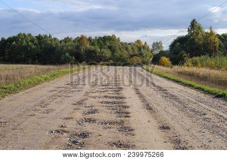 Bad Country Macadam Road With Many Pot-holes, Sunny Autumn Day