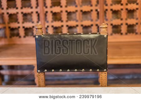 Black Leather Back Of Chair On Carved Wooden Background