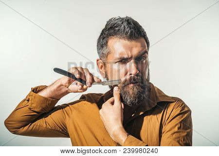 Professional Barber With Thick Beard And Mustache, Holding Straight Razor. Hairdresser Demonstrating