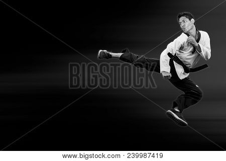 Taekwondo Man Jump Flying High Kick On Black For Poster Background With Clipping Path