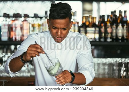 Concentrated Mixed Race Male Expert Bartender Is Placing A Cucumber Slice For A Cocktail At The Bar