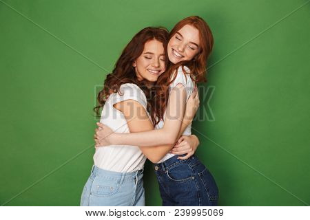 Two attractive ginger girls 20s in casual wear smiling and hugging each other with closed eyes isolated over green background poster