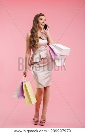 Full length photo of successful shopper woman 20s in dress smiling and speaking on mobile phone while holding shopping bags isolated over pink background