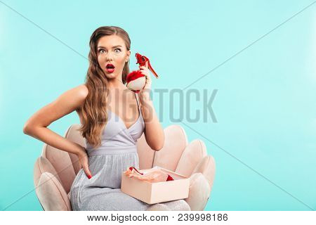 Portrait of excited shopaholic woman 20s in dress holding red shoe while sitting on armchair isolated over blue background poster