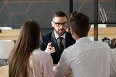 Serious investment broker, financial advisor or bank worker in suit and glasses consulting young couple giving legal advice, offering loan or presenting insurance services convincing to make deal poster