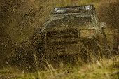 Splash of dirt under SUV on countryside road. Cross country rallying or rally raid on autumn field. Off road car takes part in racing on nature background. Extreme and four wheel drive concept poster