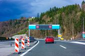 Modern LED traffic signs on Slovenian highway A1 near Trojane, red car, truck on road poster