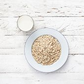 Oatmeal, rolled oats on white wooden background wilt glass of milk. Porridge oats, used in granola or muesli. Large whole flakes. Copyspace, flat lay poster