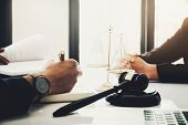 law and justice with client concept, Attorney or lawyer judgement lawsuit with holding pen, law book,gavel and scales of justice at table in office. poster