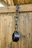 Old vintage rusty iron medieval chains or shackles, used for locking up prisoners or slaves between 1600 and 1800, on a barns wooden, background. Shackles of slaves, place of the execution of heretics poster