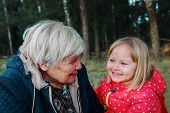 happy grandmother and granddaughter talk in nature, grandparenting poster