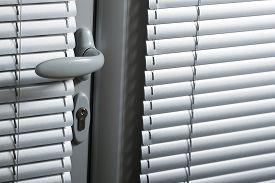 Door Handle On A Gray Door With Aluminum Shutters