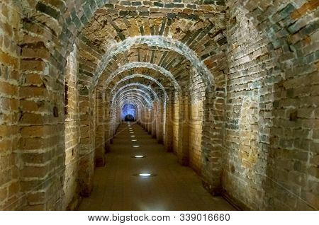 Brick archway made of red bricks as a passage between the two wings of a medieval castle. Granite stone an brick built Interior passage to bastions