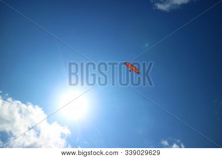 Red Paraglider Flying In The Blue Sky With The Dazzling Sun