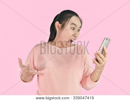 Asian Woman Angry And Furious What She See In The Smartphone, Isolated On Pink Background.