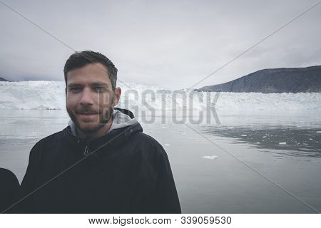 Young Traveler Tourist Sitting Standing In Front Of Huge Glacier Wall Of Ice. Icefjord Ilulissat. Ja