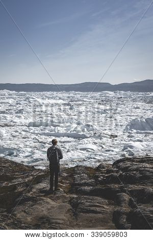 People Sitting Standing In Front Of Huge Glacier Wall Of Ice. Icefjord Ilulissat. Jakobshaven Eqip S