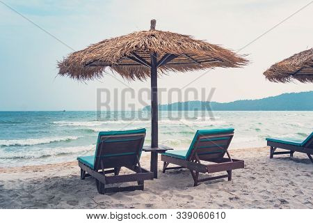 Umbrellas Made Of Straw And Chaise Longue Made Of Wood On A Wonderful Tropical Beach, Beautiful Beac