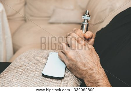 Ban Electronic Cigarettes. A Man Holds An Electronic Cigarette. Harm To Health, Replacement Of Cigar