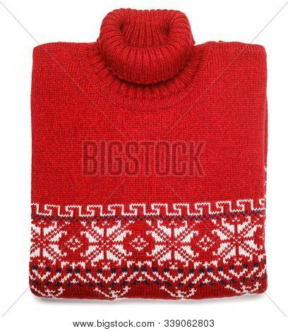 Red knitted Christmas turtleneck sweater or pullover of traditional design with white Scandinavian geometric ornament laid folded on white background
