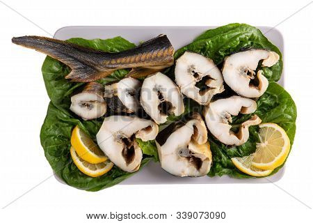 Pieces Of Sturgeon  Isolated On White Background. Fish With Lemon On Lettuce Leaves On A Gray Rectan