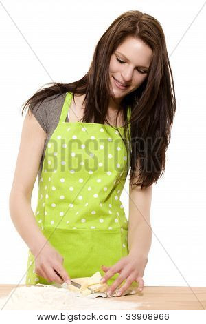 young smiling woman cutting butter or shortening for baking