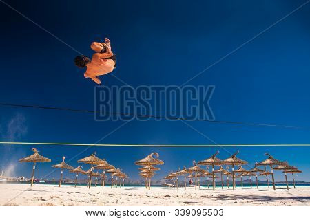 Man Jumping On Slackline On The Summer Tropical Beach. White Sand And Blue Sky In Background Slack L