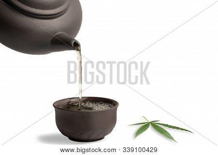 Tea Made From Cannabis Leaves ,a Glass Of Hot Marijuana Tea On White Background , Tea Pot And Cups O