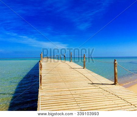 Wooden Empty Terrace Dock Or Pier. Wooden Dock Pier Blue Sea & Sky Background. View Of Wooden Dock I